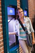 Pretty smiling student withdrawing cash smiling at camera at an ATM