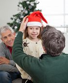 Rear view of father adjusting girl's Santa hat with grandfather looking at them in house