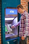 Handsome student withdrawing cash at an ATM