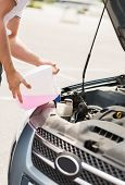 transportation and vehicle concept - man opening car bonnet and filling windscreen water tank with w