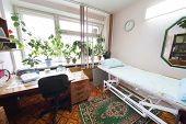 picture of infirmary  - Interior of a light doctors consulting room with a bed and a workplace - JPG