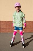 Girl in a helmet and the protection of the hands and feet riding roller skates