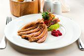 Roasted Filet Of Duck Breast Served With Salad And Cranberry Sauce