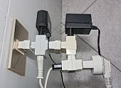 stock photo of terminator  - bunch of adapters and plugs on electrical socket  - JPG