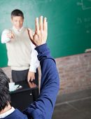 Rear view of male student raising hand to answer question in classroom