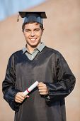 Portrait of happy young man in graduation gown holding certificate on university campus