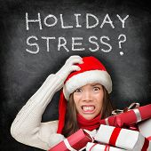 Christmas holiday stress. Stressed woman shopping for gifts holding christmas presents wearing red s