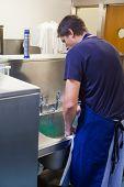 foto of porter  - Kitchen porter standing behind sink in professional kitchen - JPG