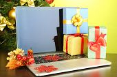 Laptop with gifts on table on green background