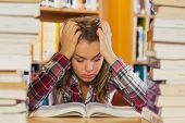 Irritated pretty student studying between piles of books in library