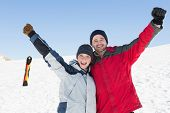 Portrait of a happy loving couple raising hands with ski board on snow in background against clear blue sky