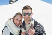Close-up portrait of a smiling couple in warm clothing in front of snowed hill
