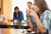 stock photo of canteen  - Female having coffee and muffin with students around table in background at  the coffee shop - JPG