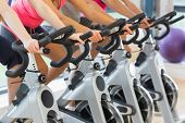 pic of exercise bike  - Mid section of four people working out at a class in gym - JPG