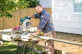 Portrait of happy mid adult carpenter cutting wood using table saw at construction site