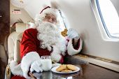 Portrait of man in Santa costume having cookies and milk in private jet