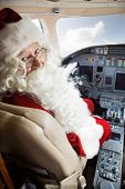Portrait of man in Santa costume sitting in cockpit of private jet