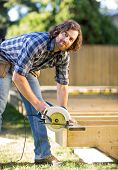 Portrait of carpenter using circular saw while building a deck