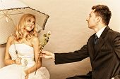 pic of enamored  - Wedding day. Portrait of romantic married couple blonde bride with umbrella and enamored groom giving a rose to girl. Studio shot sepia color vintage photo