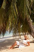 stock photo of palm-reading  - women reading under palm tree in Barbados - JPG