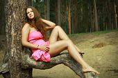 Girl In Pink Dress Relaxing On Forest Glade, Among Pines.