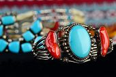 picture of cultural artifacts  - Selective focus on silver bracelet with turquoise and coral gemstones against background of several out of focus Indian artifacts - JPG