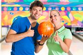 Young couple or friends, man and woman, playing bowling with a ball in front of the ten pin alley, t