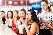 Friends or couples eating fast food and drinking milk shakes on bar in American fast food diner, the