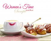 Cup of coffee with lipstick mark and croissant with strawberry jam