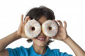 Little boy making fun with donuts on white background,