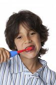Little boy is brushing his teeth on white background