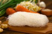 picture of glass noodles  - Raw rice noodles on wooden board with ginger and other vegetables  - JPG