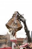 stock photo of track-hoe  - Large clamshell bucketed track hoe tearing down a former restuarant - JPG