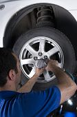 Car mechanic removing wheel nuts to change tires