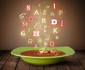 Colorful letters coming out of home cook soup bowl on wood deck