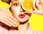 Beauty Model Girl takes Juicy Oranges. Beautiful Joyful teen girl with freckles, funny red hairstyle, yellow makeup and nails. Professional make up. Orange Slices.