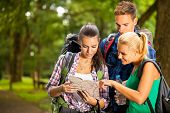 Group of  backpackers stopped on hiking trail and reading map