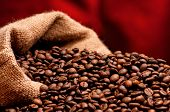 Close-up of coffee beans in burlap sack on dark red background