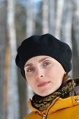 stock photo of beret  - Woman in black beret and a yellow jacket on forest background - JPG
