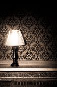 Vintage Lamp On Old Fireplace In Room With Red Rocco Pattern