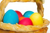 Baked basket with many Easter colored eggs
