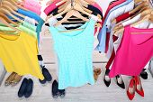 Different clothes on hangers and shoes on light background