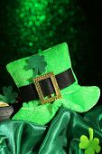 Saint Patrick day hat and pot of gold coins on green shiny background