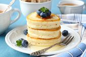 A Stack Of Scotch Pancakes With With Honey And Blueberries On A Breakfast Table