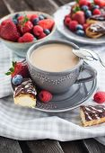 picture of eclairs  - Cup of coffee and chocolate eclairs with fresh berries - JPG