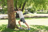 Full length side view of man doing stretching exercise against a tree in the park