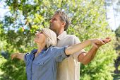 Romantic couple standing arms outstretched in park