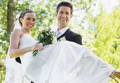 Happy groom carrying bride while looking away in garden