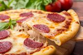 foto of takeaway  - Slice of Pepperoni Pizza  being removed from whole pizza with tomatoes in background - JPG