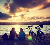 Couple with Bicycles Relaxing at Sunset